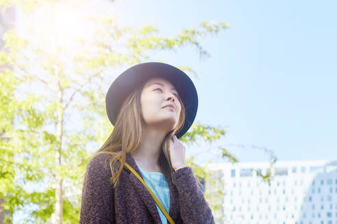 Portrait of woman at backlight wearing hat looking at distance - GEMF02994
