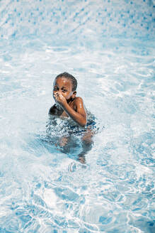 African child having fun in swimming pool, holding nose - OCMF00529