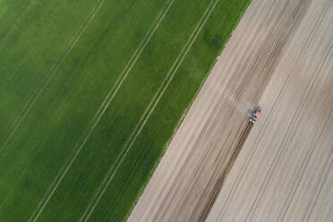 Aerial view of tractor in agricultural field, Franconia, Bavaria, Germany - RUEF02275