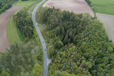 Aerial view of rural road through forest, Franconia, Bavaria, Germany - RUEF02290