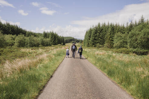 Back view of father hiking with his sons on country road, Cairngorms, Scotland, UK - NMS00327