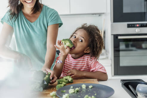 Girl cooking with mother in kitchen tasting broccoli - ERRF01667