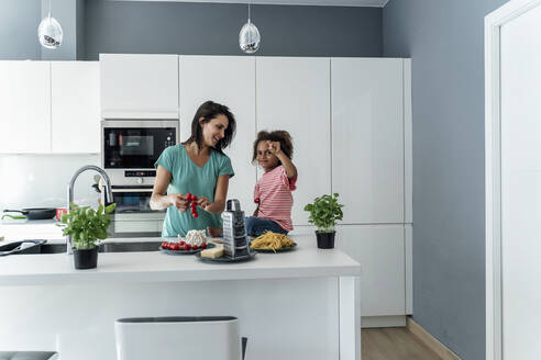 Mother and daughter cooking in kitchen together - ERRF01670