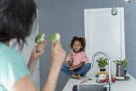 Mother showing broccoli to daughter in kitchen - ERRF01673