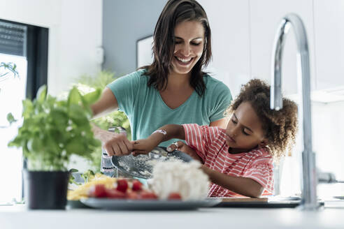 Happy mother and daughter cooking in kitchen together - ERRF01688