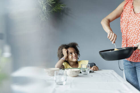 Mother serving meal for daughter sitting at dining table - ERRF01715