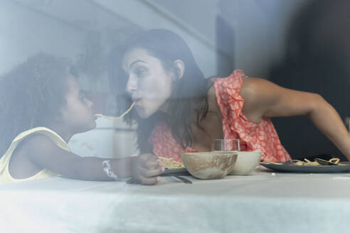 Mother and daughter eating pasta at dining table sharing a spaghetti - ERRF01721