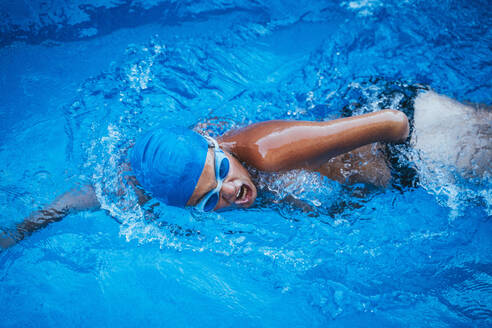 Side view of paralympic sportsman in goggles and cap without hand swimming crawl style in pool - JCMF00079