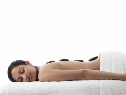 Serene woman having hot stone massage - BLEF12167
