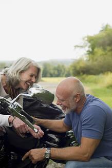 Older couple repairing motorcycle in park - BLEF12173