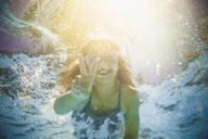 Caucasian girl swimming underwater gesturing peace sign - BLEF12206