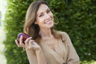 Portrait of mature woman holding an apple, hedge in the background - PNEF01781
