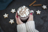 Woman's hands holding cup of Hot Chocolate with marshmellows at Christmas time - JUNF01701