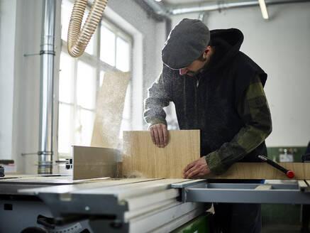 Carpenter sawing wood with circular saw - CVF01355