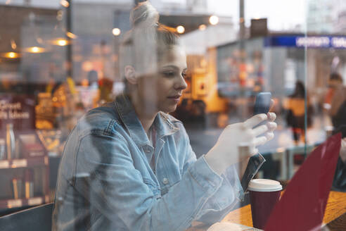 Young woman in a cafe using a smartphone - WPEF01626