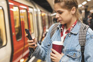 Young woman at subway station using a smartphone - WPEF01632