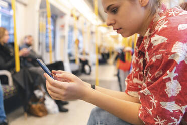 Young woman travelling by train using smartphone - WPEF01638