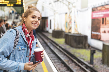 Young woman waiting for the train at station - WPEF01641