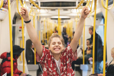 Portrait of happy young woman in the metro - WPEF01644