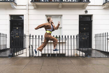 Carefree young woman jumping in front of city houses, London, UK - WPEF01650