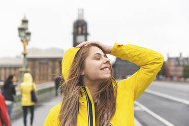 Happy young woman wearing yellow raincoat on a rainy day, London, UK - WPEF01656