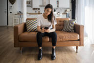 Young woman on couch at home using cell phone - GIOF06917