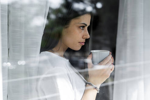 Young woman with cup of coffee behind windowpane - GIOF06941