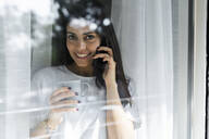 Portrait of smiling young woman on cell phone behind windowpane - GIOF06947