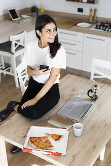 Young woman with cell phone eating pizza in kitchen at home - GIOF06950