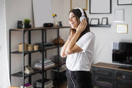 Happy young woman listening to music with headphones at home - GIOF06953