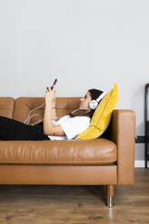 Young woman lying on the couch at home with smartphone and headphones - GIOF06956