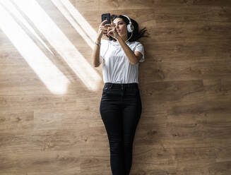 Young woman lying on the floor with smartphone and headphones - GIOF06959