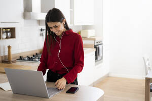 Young businesswoman with earphones using laptop at home - GIOF06968