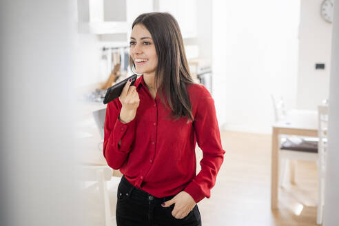 Smiling young businesswoman using smartphone at home - GIOF06971