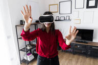 Young woman using VR glasses at home - GIOF06980