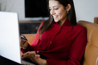 Happy young woman at home shopping online - GIOF06983