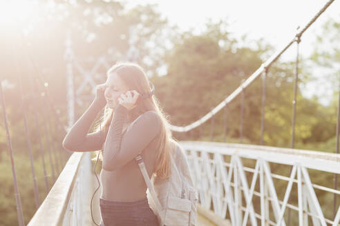 Teenage girl using smartphone and listening music on a bridge - NMS00369