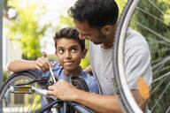 Deutschland, München, Vater 37 Jahre, Sohn 10 Jahre reparieren Fahrrad zusammen - DIGF07720