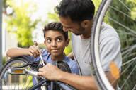 Father and son repairing bicycle together - DIGF07720