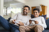 Happy father and son playing video game on couch in living room - DIGF07723