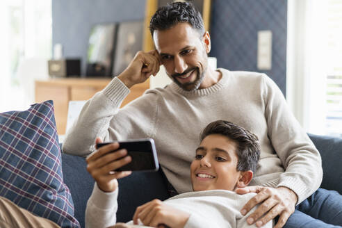 Smiling father and son using smartphone on couch in living room - DIGF07732