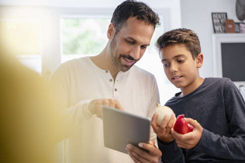 Father and son using tablet and cooking in kitchen at home together - DIGF07738