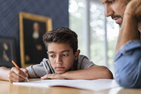Father helping son doing homework - DIGF07741