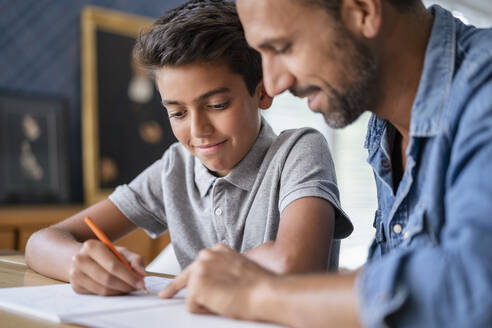Smiling father helping son doing homework - DIGF07744