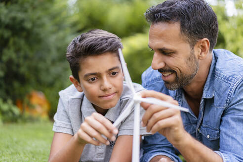 Smiling father and son lying in garden with a wind turbine model - DIGF07750