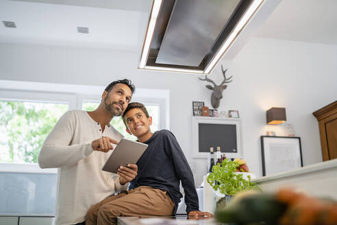 Father and son using tablet in kitchen - DIGF07771