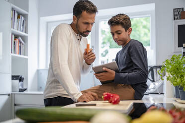 Father and son using tablet and cooking in kitchen at home together - DIGF07774