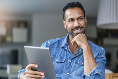 Smiling man using tablet at home - DIGF07783