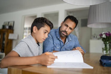 Father helping son doing homework - DIGF07786