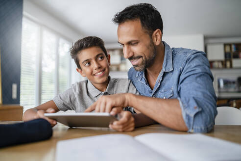 Father and son using tablet and doing homework - DIGF07789